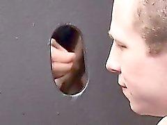 Cody Marsh kneeling before a wall of glory holes, slurping